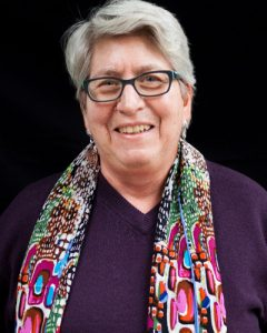 A portrait of Bettina wearing a scarf is shown.