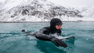 A surfer in a full-body wetsuit paddles on a board in icy water in front of a snowy hill