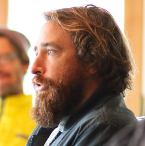 A profile image of Trey Highton looking to the left with beard and mid-length blonde hair